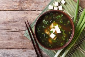 Bowl of miso soup, with spring onion, tofu and chopsticks. On a wooden background.