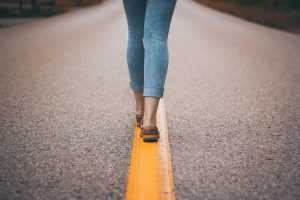 Woman's feet walking down the middle of the road